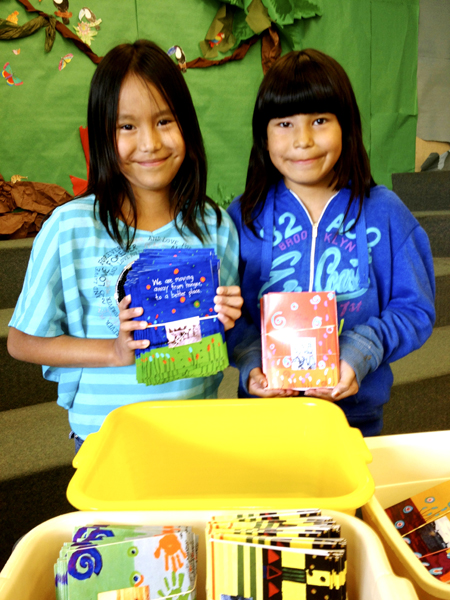 Students Rain Goodstoney (left) and Serenity Fox help with the packaging of card